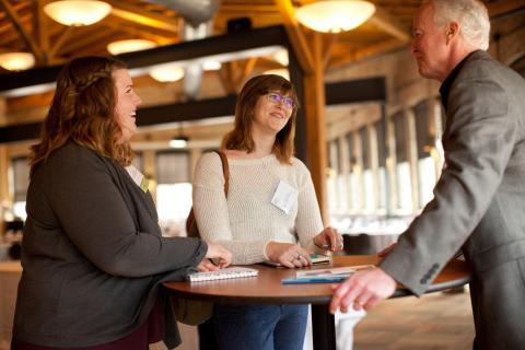 Three people conversing at a standing table.